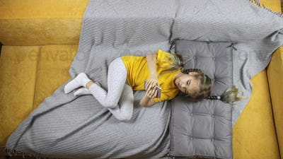 Kid on yellow sofa with gray blanket and using smartphone for online chatting and distant learning