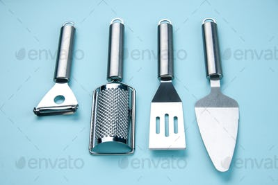 Side view of stainless kitchen tools on soft blue color background with free space