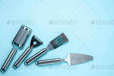 Above view of stainless kitchen tools on the right side on soft blue color background with free