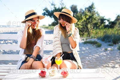 Outdoor portrait of company happy funny hipster girls going crazy on the beach cafe
