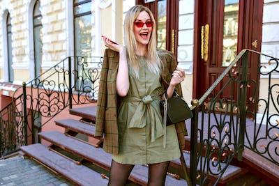 Outdoor fashion image of stunning blonde model woman posing on the Paris street