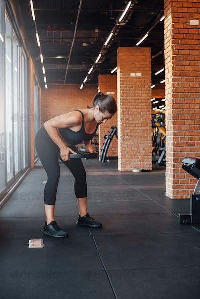 Female bodybuilder trains lifting a dumbell in modern gym