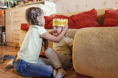 Happy kids has made a crown with cardboard pack and playing with it in role games