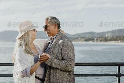 Happy senior couple dancing by the sea