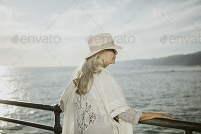 Senior woman on the pier by the sea