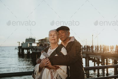 Senior couple intimately embracing by the sea