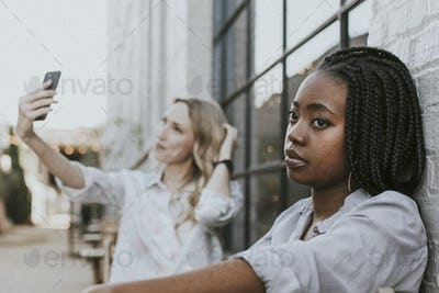 Black woman getting bored of her blond friend keep taking a selfie