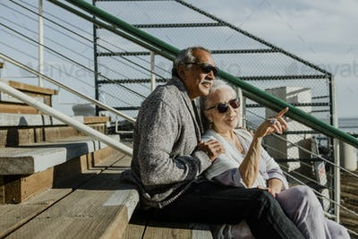 Senior couple sitting together by the sea