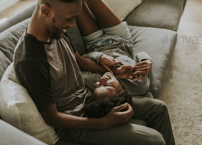 African couple chilling in a living room at home