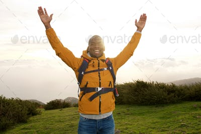 happy african american backpacker standing outdoors with hands raised