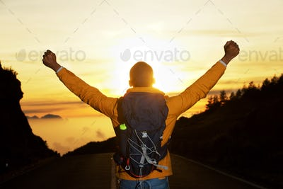 back of man with backpack with arms raised during sunset