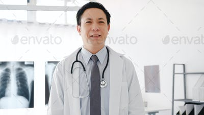 Young Asia male doctor in white medical uniform with stethoscope looking at camera