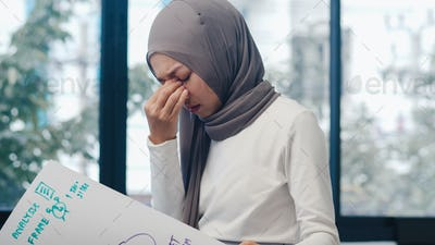 Asia muslim lady drawing work plan think information reminder on paper in new normal office