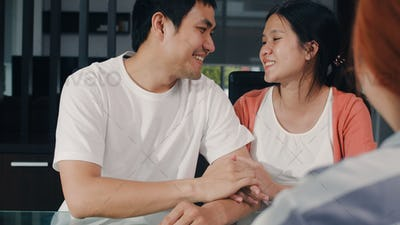 Young Asian Pregnant couple sign contract documents at home