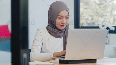 Asia muslim lady casual wear working using laptop in modern new normal office.