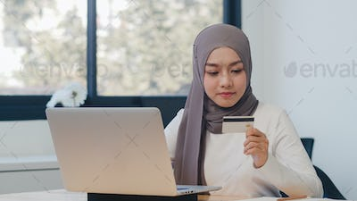 Asia muslim lady using laptop, credit card buy and purchase e-commerce internet in office.