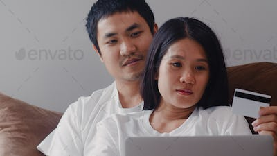 Young Asian Pregnant couple online shopping at home.