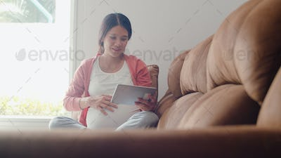 Young Asian Pregnant woman using tablet search pregnancy information.