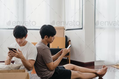 Happy young Asian gay couple relocation removals settle in new home.