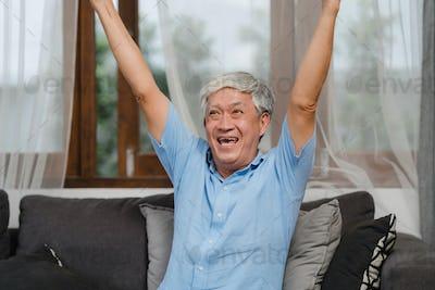 Asian senior men play games at home.