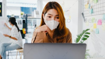 Asia businesswoman wear face mask using laptop presentation to colleagues in video call in office.