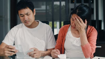 Young Asian Pregnant couple records of income and expenses at home.