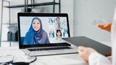 Young Asia female doctor using laptop talking video conference call with patient at hospital.