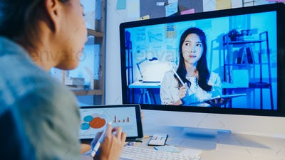 Asia businesswoman using desktop talk to colleagues in video call meeting at living room.