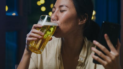Young Asia lady drinking beer having happy night party event online celebration at home.