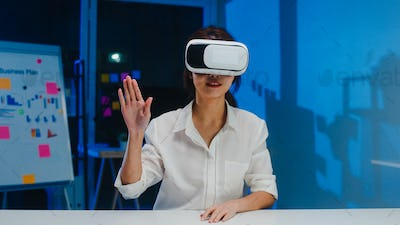 Young asian female using vr glasses (virtual reality) testing mobile app at home office night.