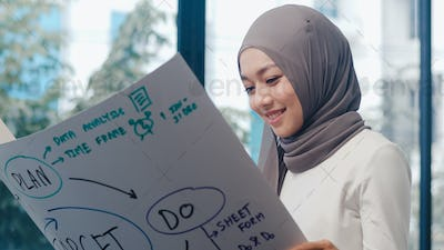 Asia muslim lady drawing work plan think information reminder on paper in new normal office.