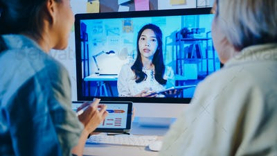 Asia businesswomen using desktop talk to colleagues in video call meeting at living room.