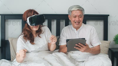 Asian senior couple using tablet at home.