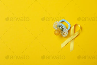 Pacifier and child cancer awareness ribbon on yellow background
