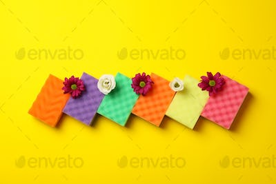 Color sponges for cleaning and flowers on yellow background