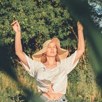 Slow Living concept New Lifestyle Trend. Relaxing young woman with lowers in nature, in corn