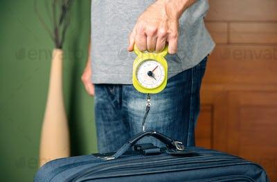 Man checking luggage weight with steelyard balance