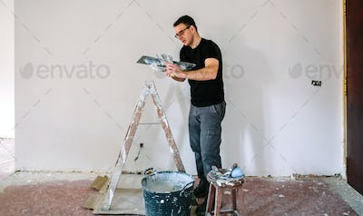 Builder working picking plaster with spatula
