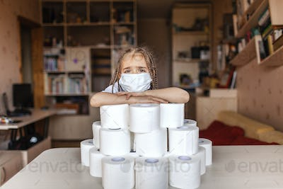 A girl wearing respirator mask sitting near the heap of toilet paper, prepare for self-isolation
