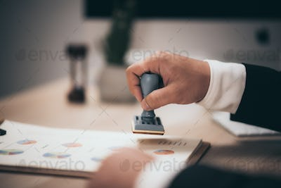 Young business man appoval stamper stamp on paper business contract, loan money approved.