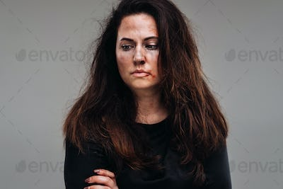 a battered woman in black clothes on an isolated gray background. Violence against women