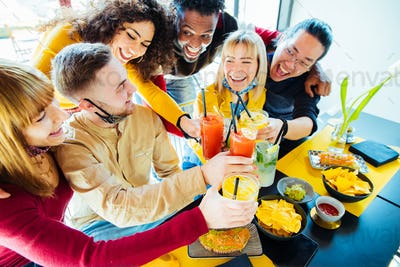 Multiracial friends wearing face masks drinking cocktails at bar restaurant