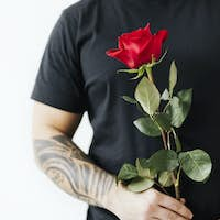 Tattooed man with a rose background