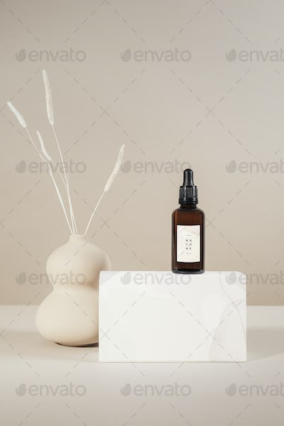 Brown glass dropper bottle with a white box product mockup