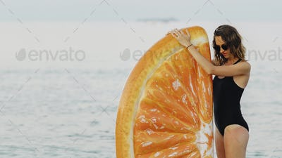 Girl with an inflatable orange