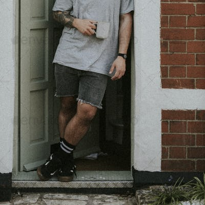 Man having a coffee by his doorway, watching the outside world