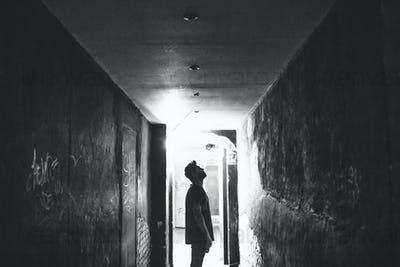 Tattooed man staring at the walls in a dark alley