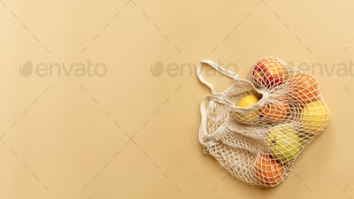 Reusable net bag with fruits on an orange background