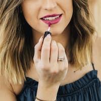 Blond beauty blogger applying liquid lipstick