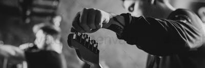 Man on the stage tuning his guitar